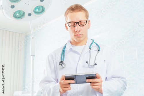 Physician works on a tablet computer in a clinic