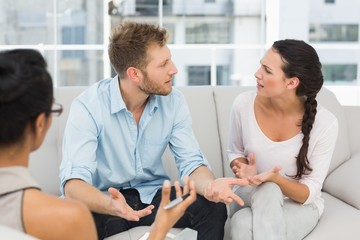 Unhappy couple arguing at therapy session
