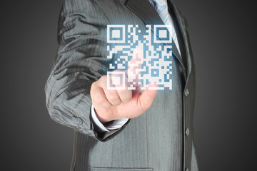 Businessman with hand pressing virtual qr code button