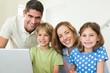 Portrait of happy family using laptop