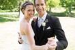 Happy bride and groom dancing together in garden