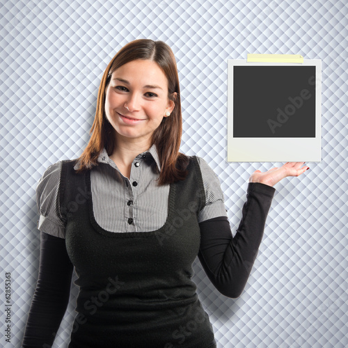 Young pretty woman holding a photo over textured background
