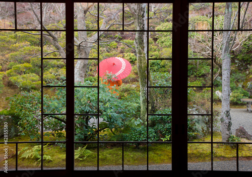 A person stands protected by an umbrella in a courtyard garden, Kyoto, Japan