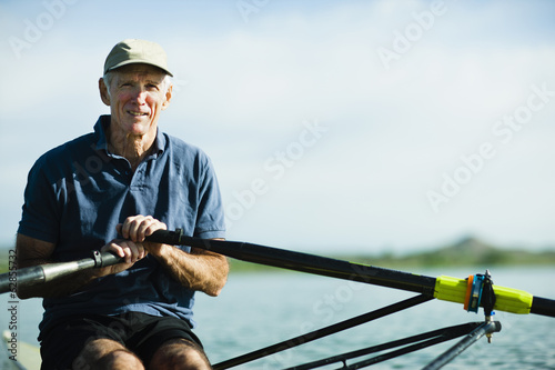 A middle-aged man rowing a single scull rowing boat on the water.