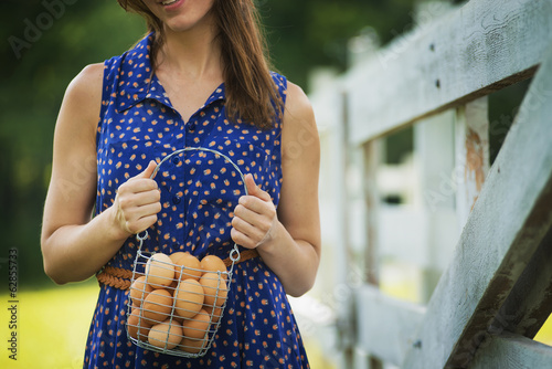 A woman holding a basket of hen's eggs gathered from the chickens on a farm.