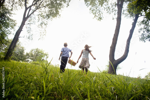 Two children running through the fields with a basket.