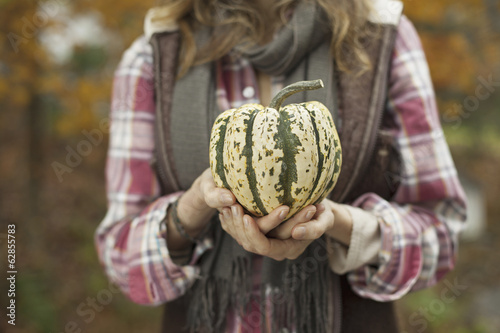 Organic farm. A woman holding a large striped squash vegetable.
