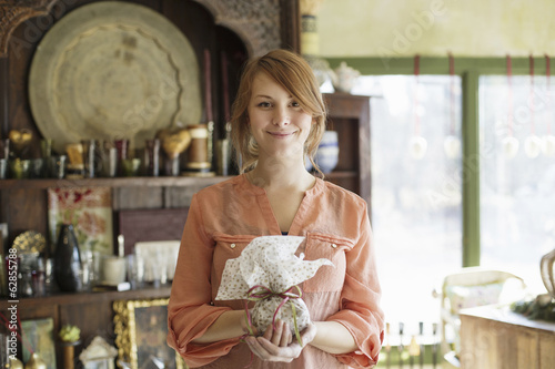 A young woman standing in a store full of antique objects, holding a tied packet with ribbon.