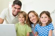 Portrait of happy family using laptop