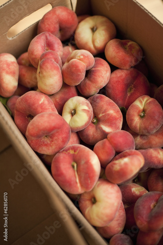 Fresh fruit on an organic farm stand. Doughnut peaches in a box.