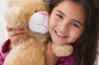 canvas print picture - Young smiling girl with stuffed toy