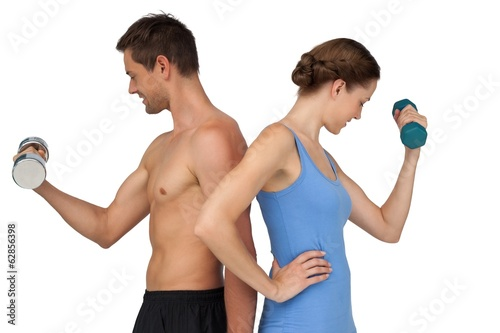 Fit young couple exercising with dumbbells
