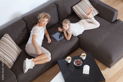 Mother and daughter with tablet resting on the couch.