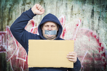 Demonstrator with a tape on a mouth and poster near to the wall