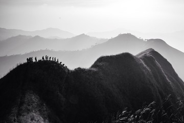 silhouette of trekker on top of mountain in black and white