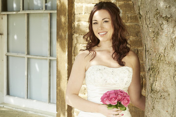 Female bride standing against sunny wall and tree