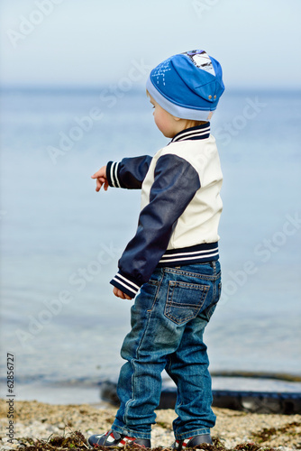 boy dropping stones in the sea