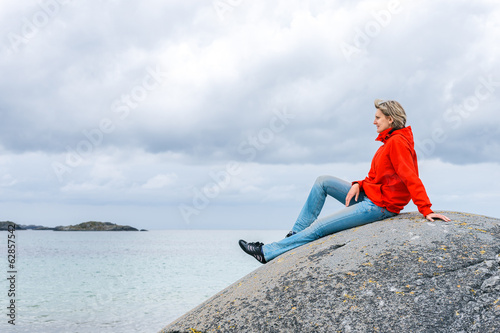 Woman sitting on stone and enjoying sea view