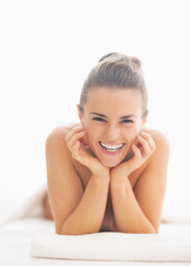 Portrait of smiling young woman on massage table