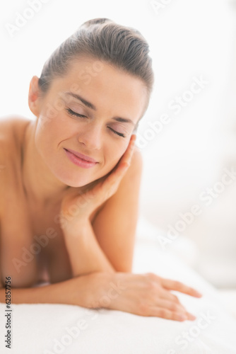 Happy young woman relaxing on massage table