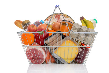 Shopping basket full of groceries isolated on white.