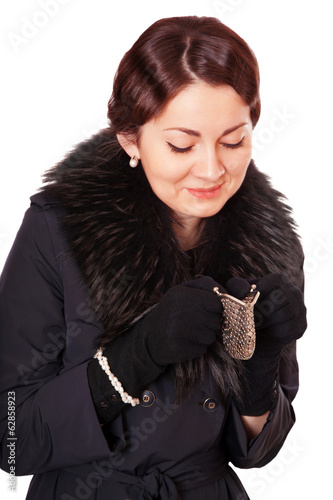 Luxury woman in a coat looks into an empty wallet