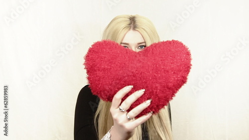 Beautiful blonde woman brings red heart to the camera