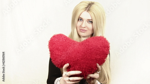 Beautiful smiling blonde woman holding red heart
