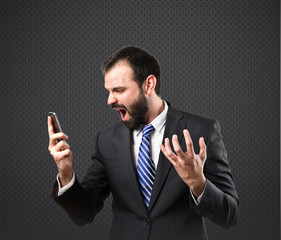 Young businessmen shouting to mobile over black background.