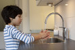 Eight year old boy washing hands