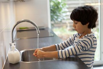 Eight year old boy washing hands