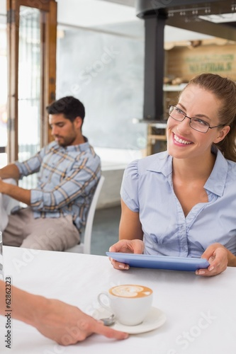 Smiling woman receiving coffee while using digital tablet in