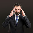 Young businessman with headache over black background