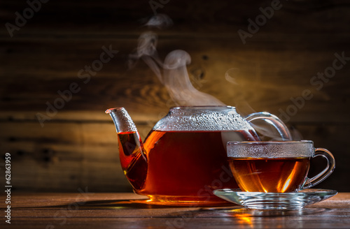 Foto op Canvas Thee glass teapot and mug on the wooden background