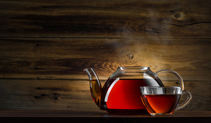 glass teapot with black tea on wooden background