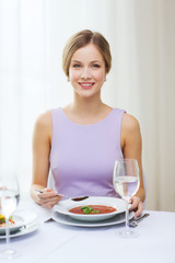 smiling young woman eating appetizer at restaurant