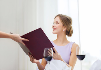 smiling woman recieving menu from waiter