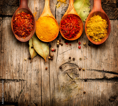 Spices. Curry, saffron, turmeric, cinnamon over wood