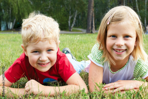 boy and girl lying on green grass