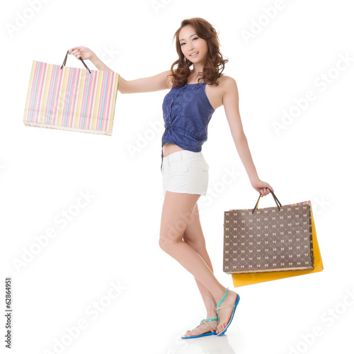 Exciting Asian shopping woman holding bags