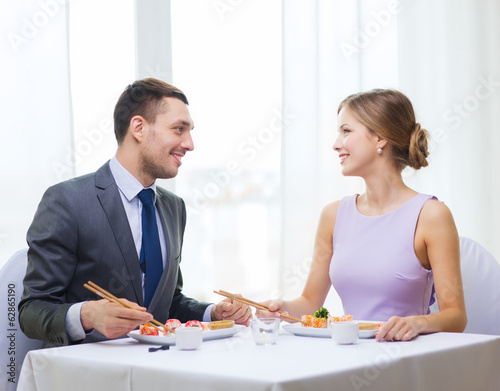 smiling couple eating sushi at restaurant