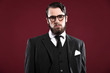 Retro 1900 fashion man with beard wearing grey suit black tie an