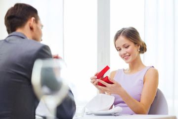 excited young woman looking at boyfriend with box