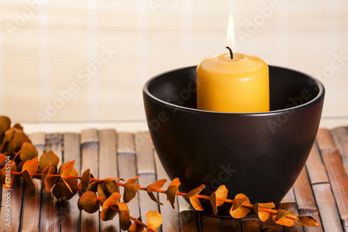 Aroma candle in black ceramic bowl on bamboo mat and dry leafs