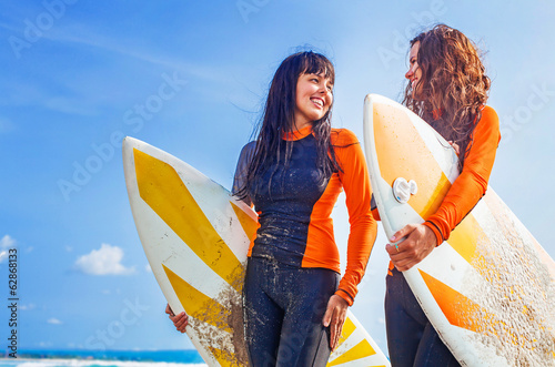 Surfer girls discussing something and smiling