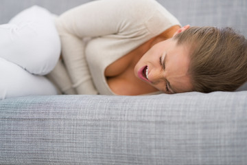 Young woman with stomach ache laying on sofa