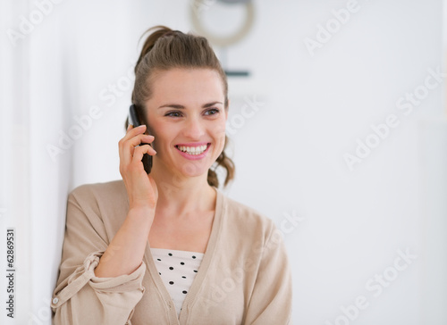 Portrait of happy young woman talking mobile phone