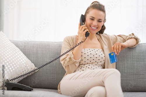 Smiling young woman with credit card talking phone