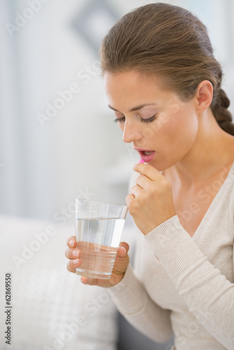 Portrait of young woman taking pill