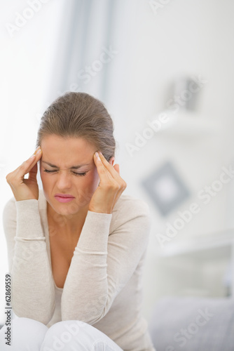 Young woman with head ache sitting on couch